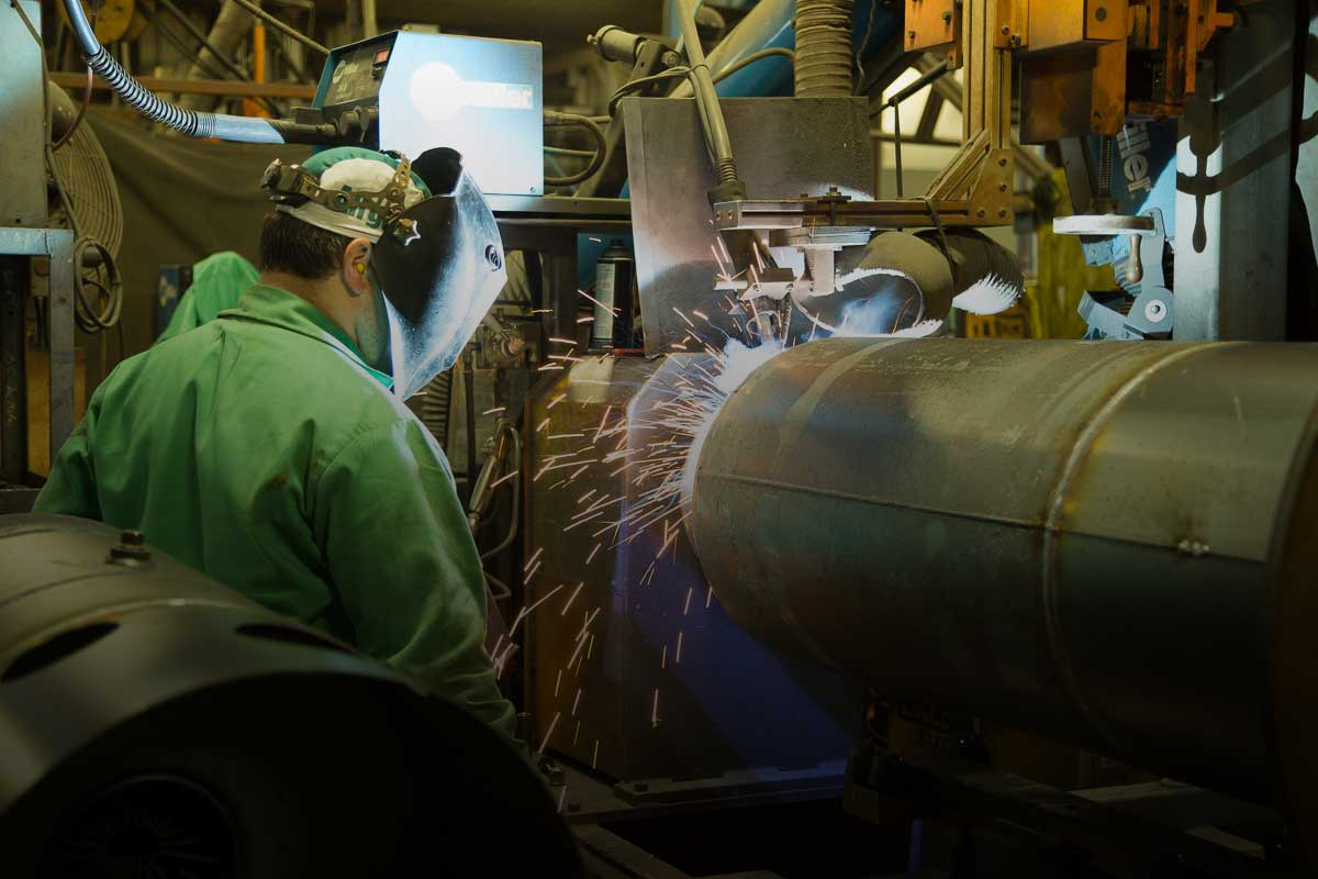 Male employee welding a tank